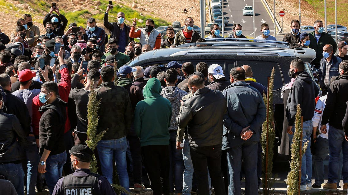 Angry people prevent passage to the vehicle of parliamentarians as it approaches al-Hussein New Salt Hospital in the town of Salt, northwest of Jordan's capital, on March 13, 2021. (AFP)