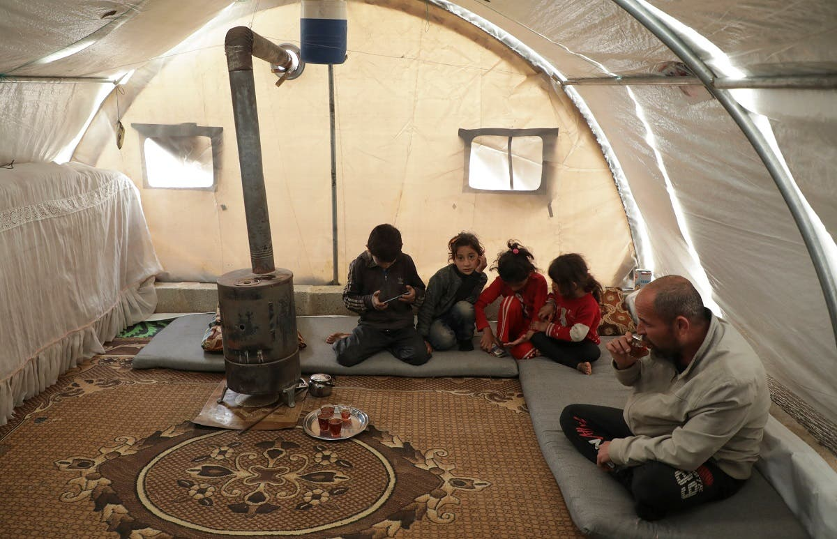 Mohammed Abu Rdan sits with his family inside a tent, at an internally displaced Syrian camp, in northern Aleppo, Syria March 11, 2021. (Reuters/Mahmoud Hassano)