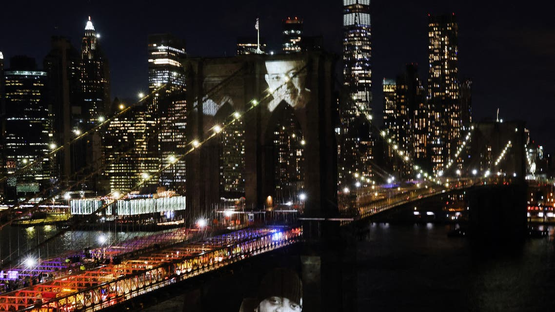 """aces of victims of Covid-19 are projected onto the Brooklyn Bridge during a memorial service called """"A COVID-19 Day of Remembrance"""" on March 14, 2021 in New York City. (File photo: AFP)"""