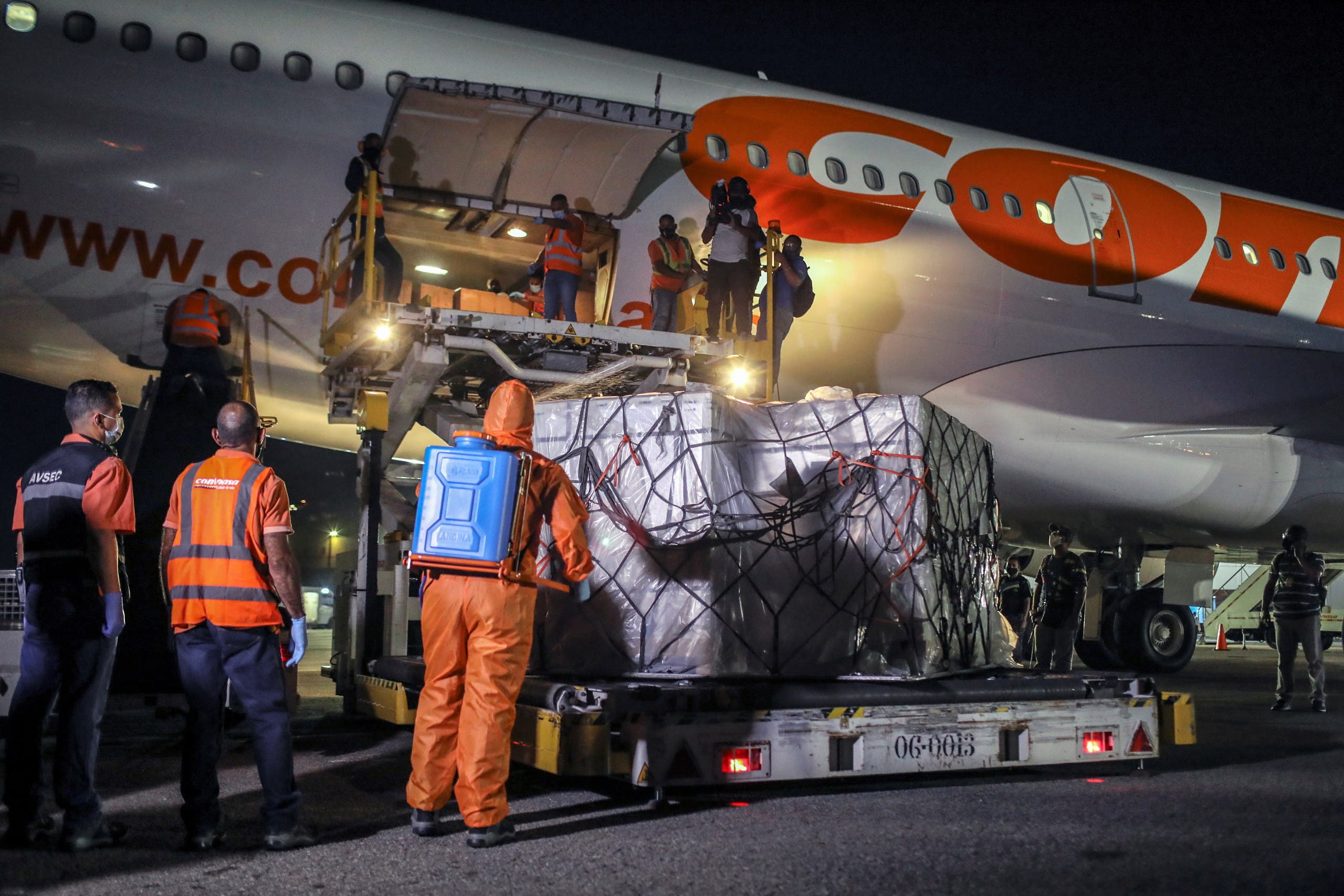 Boxes (in white) containing China's Sinopharm vaccine against the coronavirus disease (COVID-19) are unloaded from a plane upon arrival in Caracas, Venezuela March 1, 2021. (Reuters)