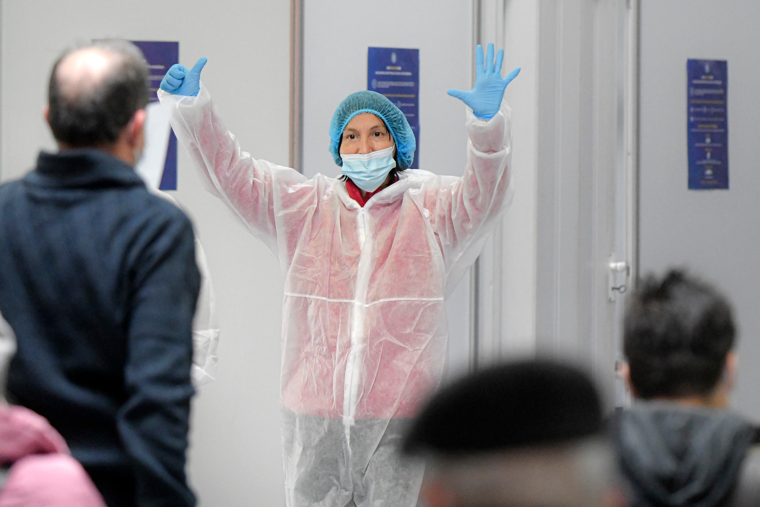 A member of the medical team gestures to indicate the number of the vaccination booth, at a Pfizer-BioNTech COVID-19 vaccination center in Bucharest, Romania, Wednesday, Jan. 20, 2021. (AP)
