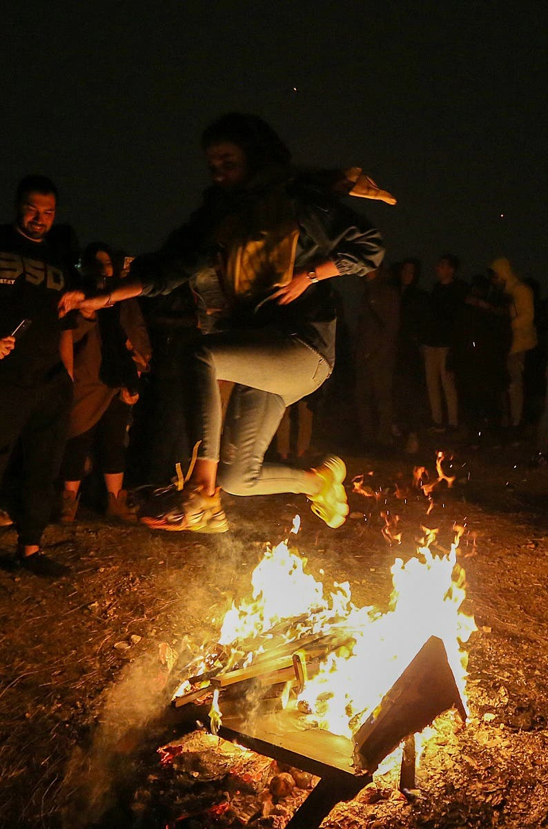 An Iranian jumps over the bonfire in Tehran on March 16, 2021 during the Wednesday Fire feast, or Chaharshanbeh Soori, held annually on the last Wednesday eve before the Spring holiday of Noruz. (AFP)