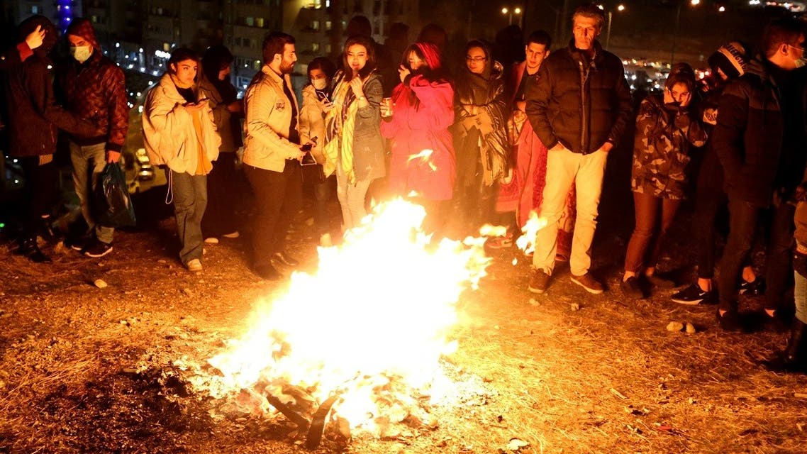 Iranian families light fire outside their houses in Tehran on March 16, 2021 during the Wednesday Fire feast, or Chaharshanbeh Soori, held annually on the last Wednesday eve before the Spring holiday of Noruz. (AFP)