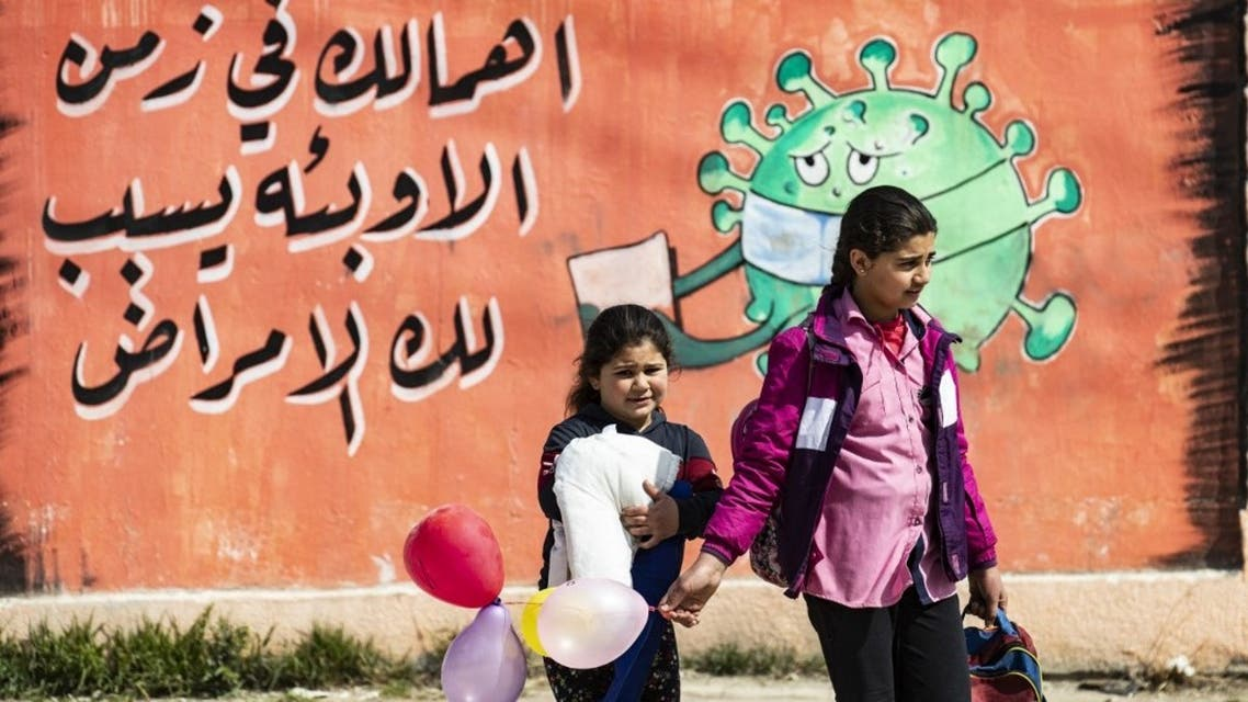 Syrian children cross a road in front of a mural awareness campaign drawing calling on people to take care as the COVID-19 pandemic spreads all over the world in Syria's northeastern city of Qamishli on March 9, 2021. (AFP)