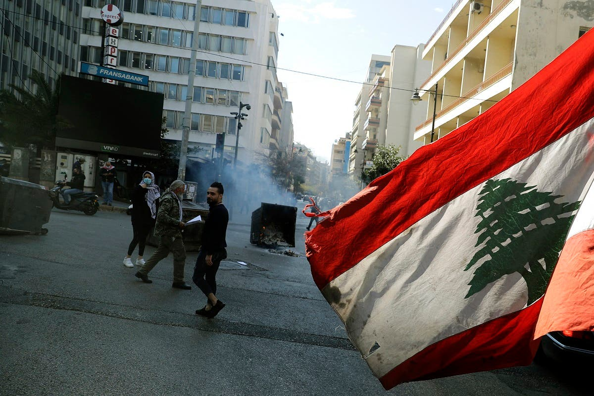 An anti-government demonstrator waves the national flag as they block the street, with burning garbage dumpsters, in front of Lebanon's central bank in the capital Beirut on March 16, 2021. (File photo: AFP)