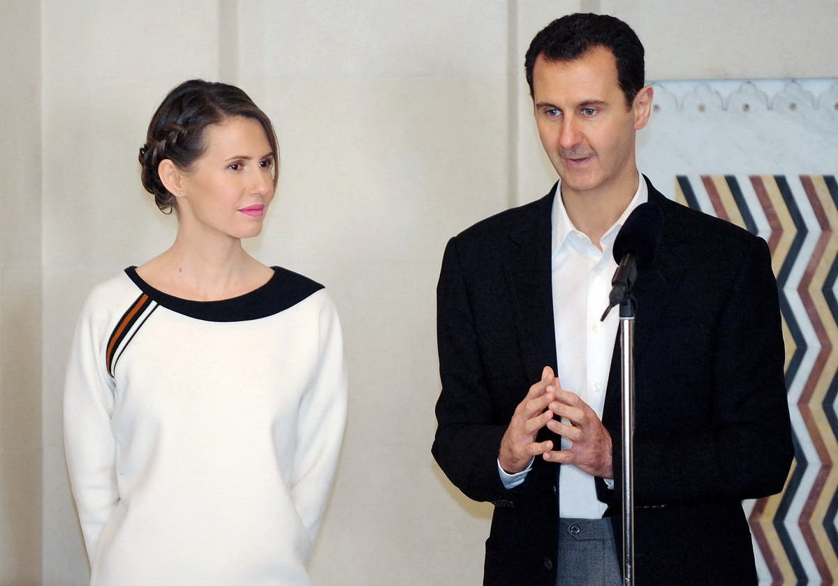 A file photo shows Syrian President Bashar al-Assad (R) speaking next to his wife Asma in the capital Damascus on March 21, 2016. (Stringer/SANA/AFP)