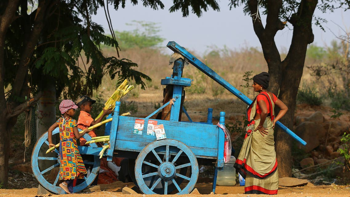 Indian children help a woman to extract juice from sugarcane as she sells them by a roadside on the outskirts of Hyderabad, India, Tuesday, March 16, 2021. (File photo: AP)