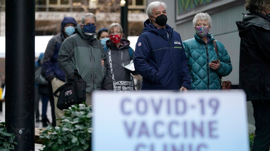 People stand near a sign as they wait in line to receive the first of two doses of the Pfizer vaccine for COVID-19, at a one-day vaccination clinic set up in an Amazon.com facility in Seattle and operated by Virginia Mason Franciscan Health.  (AP)
