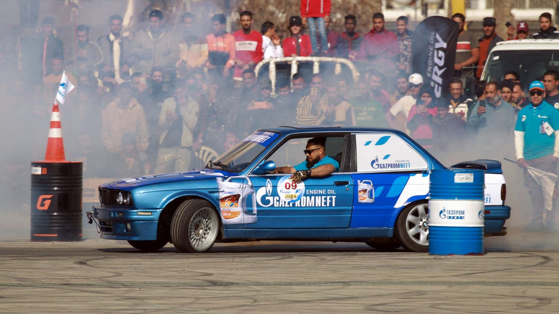 Libyans watch a driver put his drifting skills to the test during a competition in the coastal city of Benghazi, on March 12, 2021.