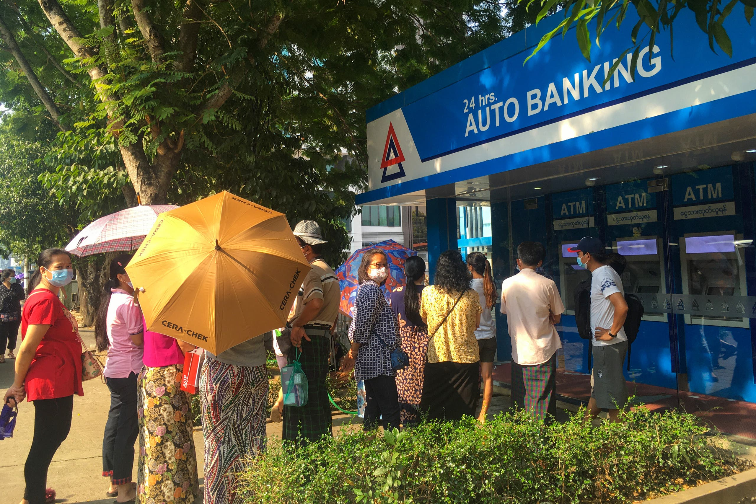 People queue as they wait to withdraw money from automated teller machines (ATM) of KBZ Bank in Yangon on March 18, 2021, amid strained banking operations due to the mass protests against the February military coup. (File photo: AFP)