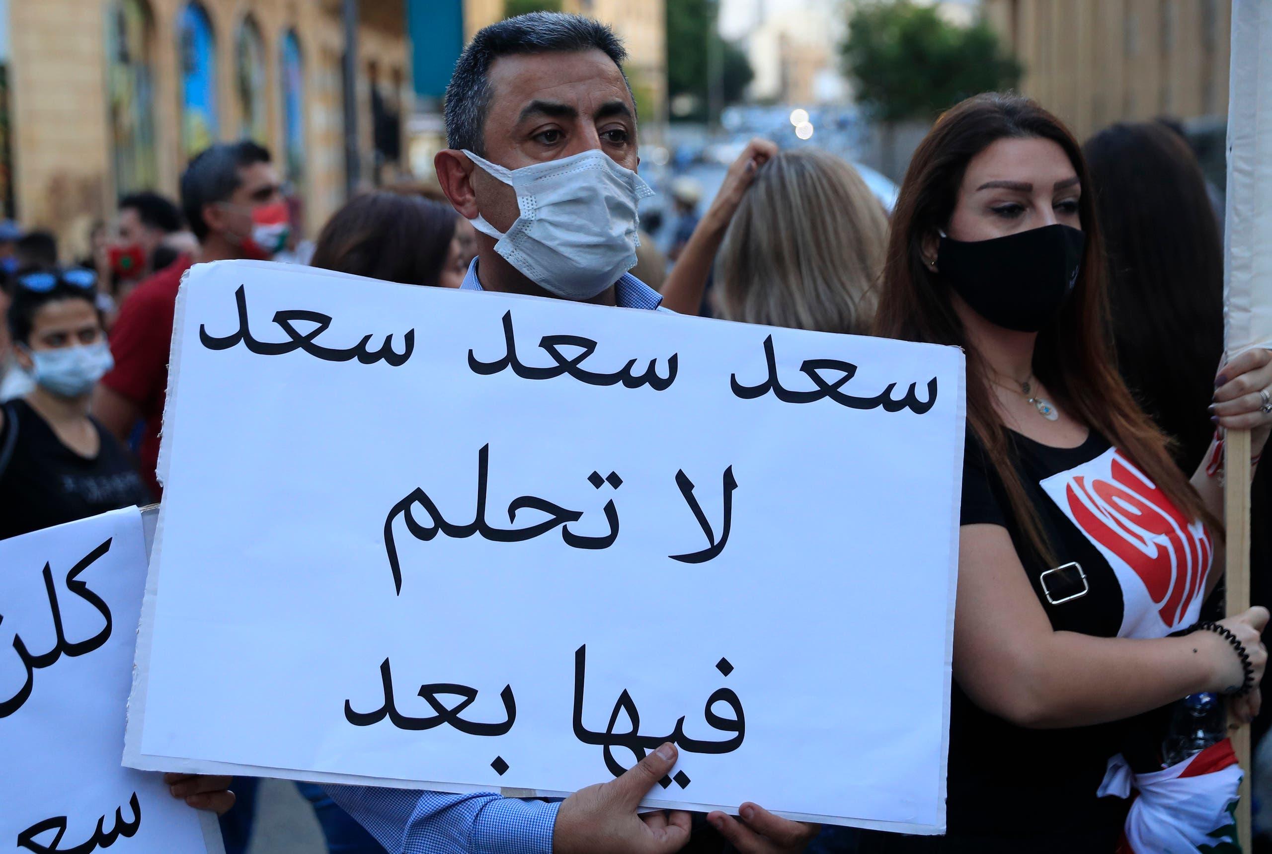 مواطنون يرفعون يافطة ضد عودة سعد الحريري للحكومة (أرشيفية- أسوشييتد برس)
