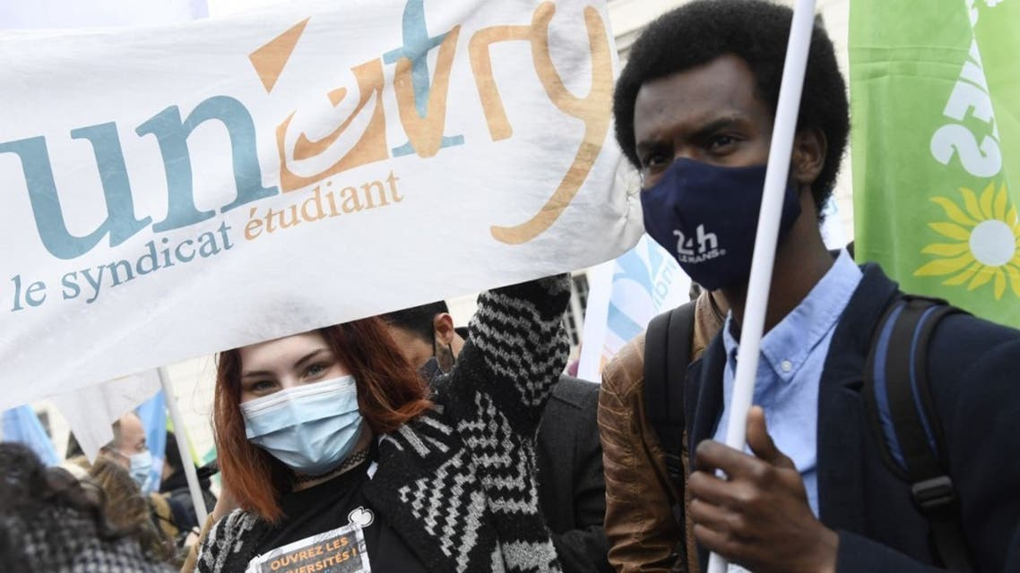 Protestors hold a Unef students union's banner during a demonstration of young people against the precariousness of students, accentuated by the Covid-19, in Paris on March 16, 2021. (AFP)