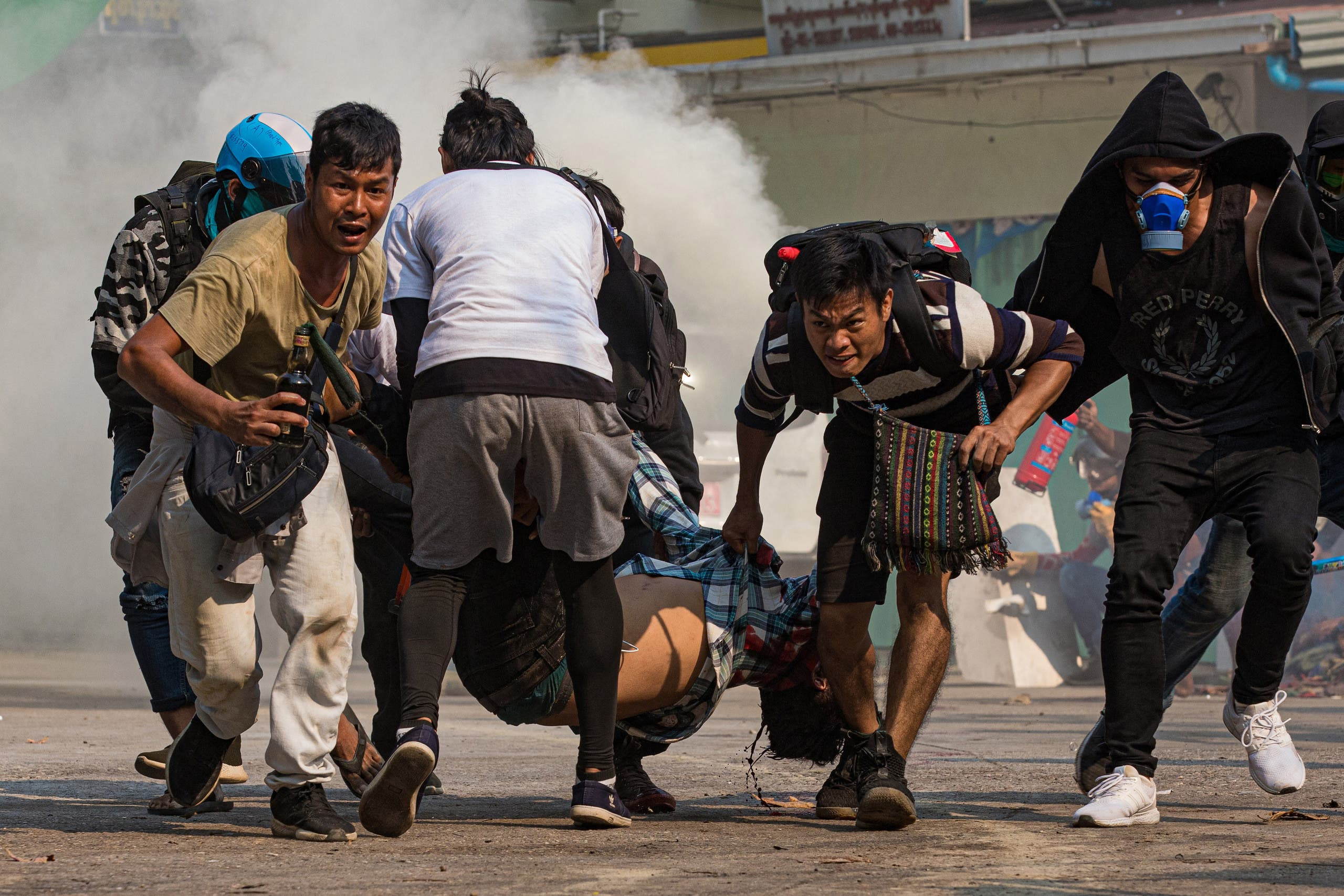 Protesters carry a wounded man shot with live rounds by security forces during a crackdown on demonstrations against the military coup in Yangon on March 17, 2021 (File photo: AFP).