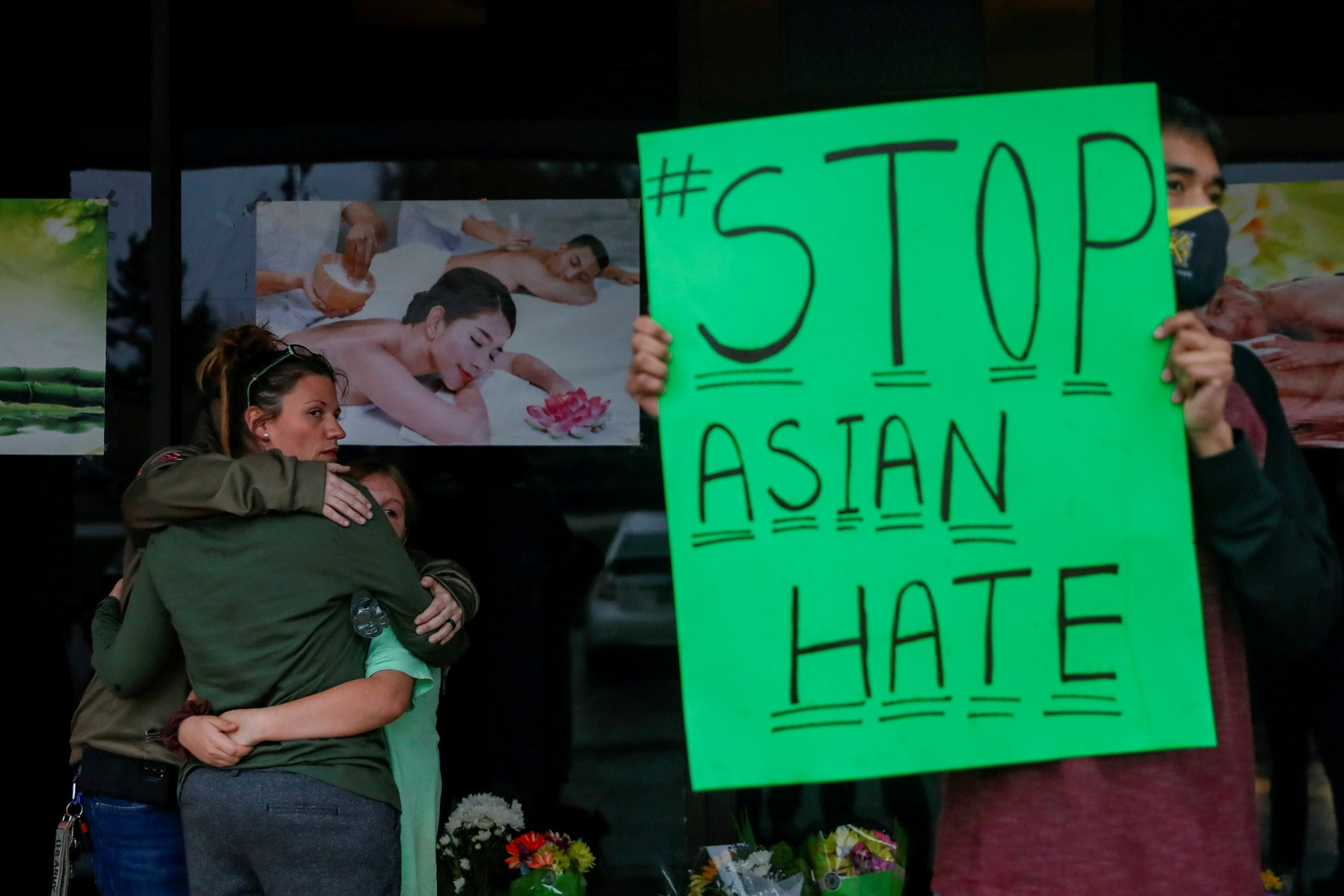 People grieve while Jesus Estrella, 21 holds a sign outside Young's Asian Massage following the deadly shootings in Acworth, Georgia, U.S. March 17, 2021. (Reuters)