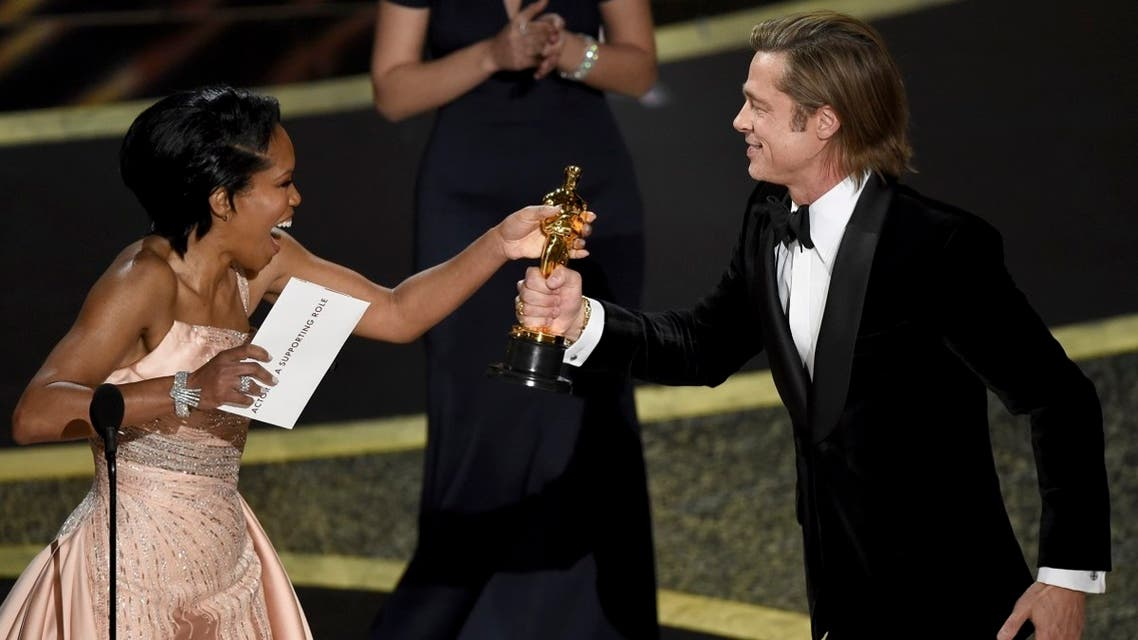 """Regina King (left), presents Brad Pitt with the award for best performance by an actor in a supporting role for """"Once Upon a Time in Hollywood"""" at the Oscars on February 9, 2020, at the Dolby Theatre in Los Angeles. (AP)"""