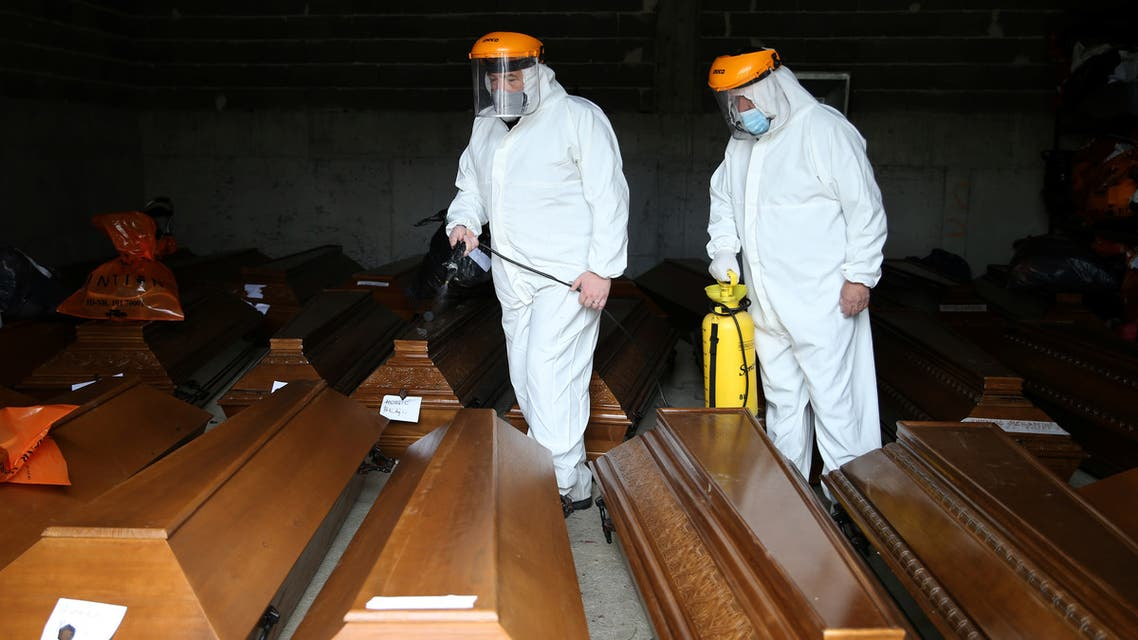 Cemetery workers disinfect coffins at an improvised morgue for coronavirus disease (COVID-19) victims at the Bare cemetery in Sarajevo, Bosnia and Herzegovina March 19, 2021. REUTERS/Dado Ruvic