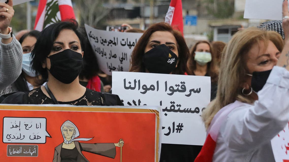 Lebanese women hold placards protesting against the country's deep economic crisis in Beirut on the occasion of Mother's Day on March 20, 2021. (File photo: AFP)