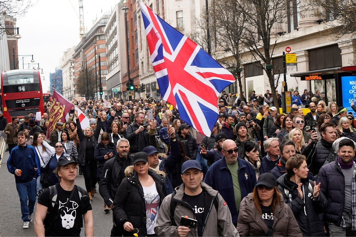 Demonstrators march against the ongoing coronavirus restrictions during an anti-lockdown protest in central London on March 20, 2021. (Niklas Halle'N/AFP)