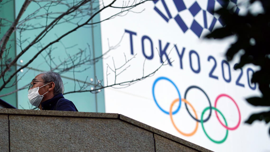 A man wearing a protective mask to help curb the spread of the coronavirus walks near the banner for the Tokyo 2020 Olympic Games Thursday, Feb. 25, 2021. (File photo: AP)