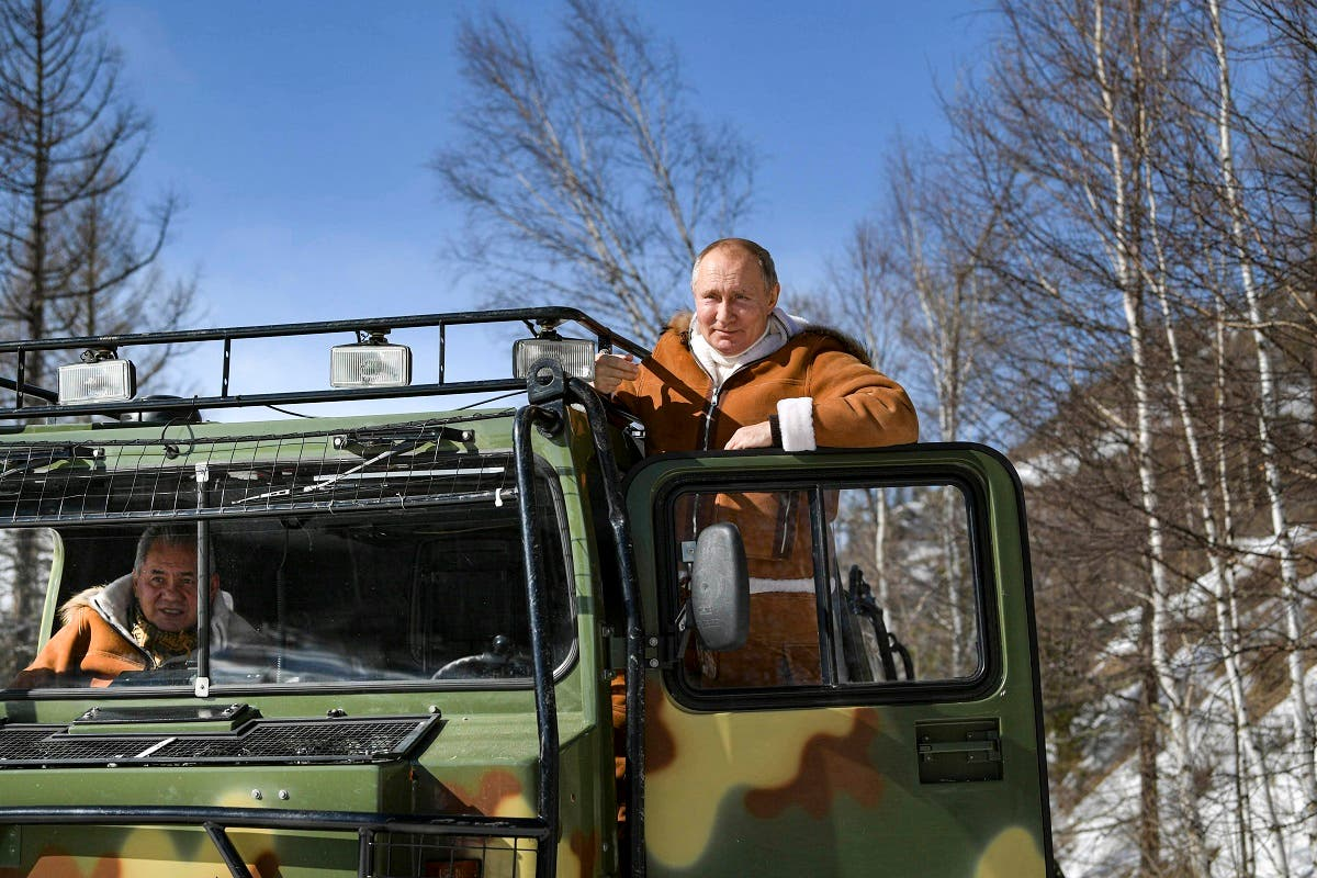 Russian President Vladimir Putin drives a tracked all-terrain vehicle as Russia Defense Minister Sergei Shoigu sits inside, in a taiga forest in Russia's Siberian. (Alexei Druzhinin, Sputnik, Kremlin Pool Photo via AP)