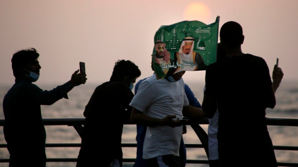 Saudis watch the sunset as they wave a flag with pictures of Saudi King Salman, right, and Crown Prince Mohammed bin Salman during a celebration marking National Day to commemorate the unification of the country as the Kingdom of Saudi Arabia. (AP)