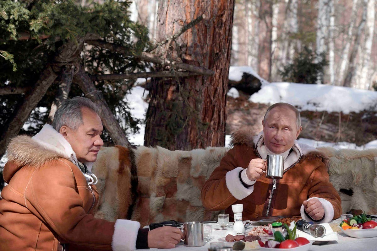 Russian President Vladimir Putin, right, and Russian Defense Minister Sergei Shoigu have a meal and drinks in a taiga forest in Russia's Siberian region in Russia, Sunday, March 21, 2021. (Alexei Druzhinin, Sputnik, Kremlin Pool Photo via AP)