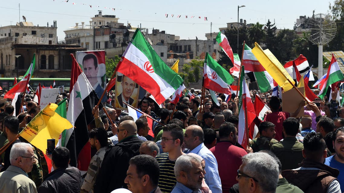 Syrians wave the Russian and Iranian flags and carry portraits of President Bashar al-Assad as they gather in Aleppo's Saadallah al-Jabiri square on April 14, 2018, to condemn the strikes carried out by the United States, Britain and France against the Syrian regime.