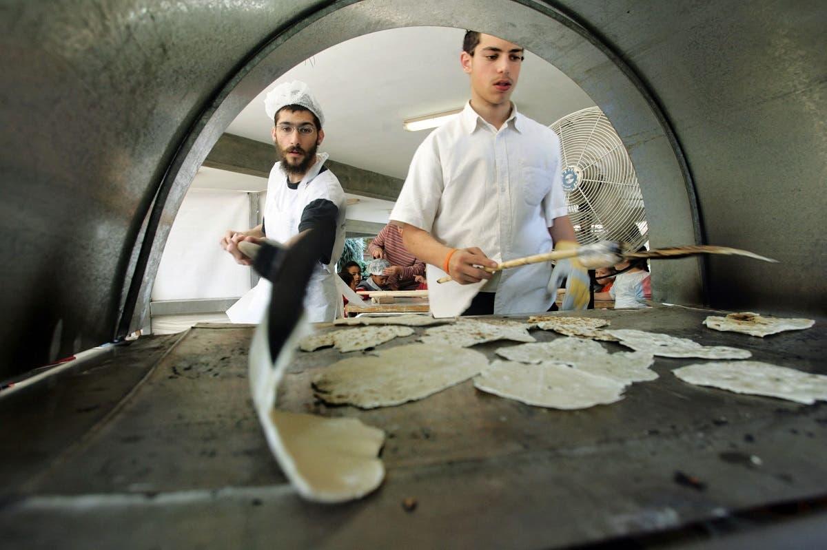 Ultra-Orthodox Jewish settlers prepare Matzah bread, traditional handmade Passover unleavened bread, in the Jewish settlement of Neve Dekalim in the Gush Katif settlement block in the Gaza Strip Monday, April 11, 2005. (AP)