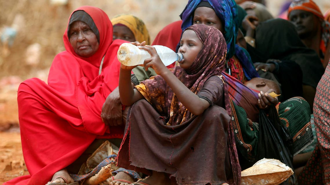 Internally displaced Somali women wait for relief food while a child drinks water at a distribution centre organized by a Qatar charity after fleeing from drought stricken regions in Baidoa, west of Somalia's capital Mogadishu. (File photo: Reuters)