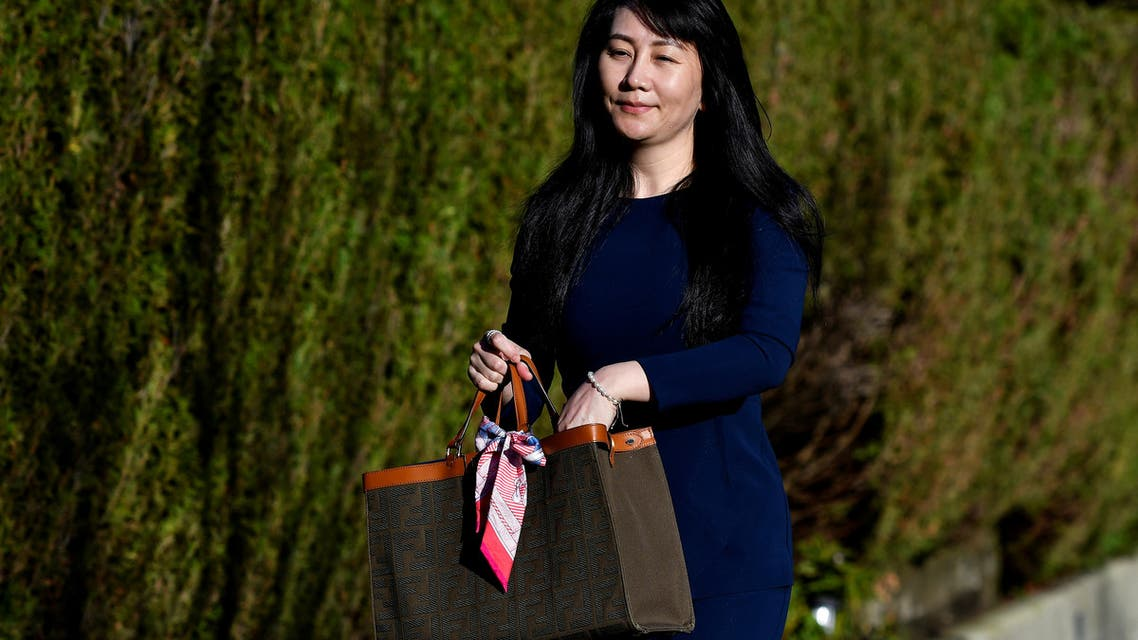 FILE PHOTO: Huawei Technologies Chief Financial Officer Meng Wanzhou reaches into her bag for a face mask as she leaves her home to attend a court hearing in Vancouver, British Columbia, Canada March 15, 2021. REUTERS/Jennifer Gauthier/File Photo