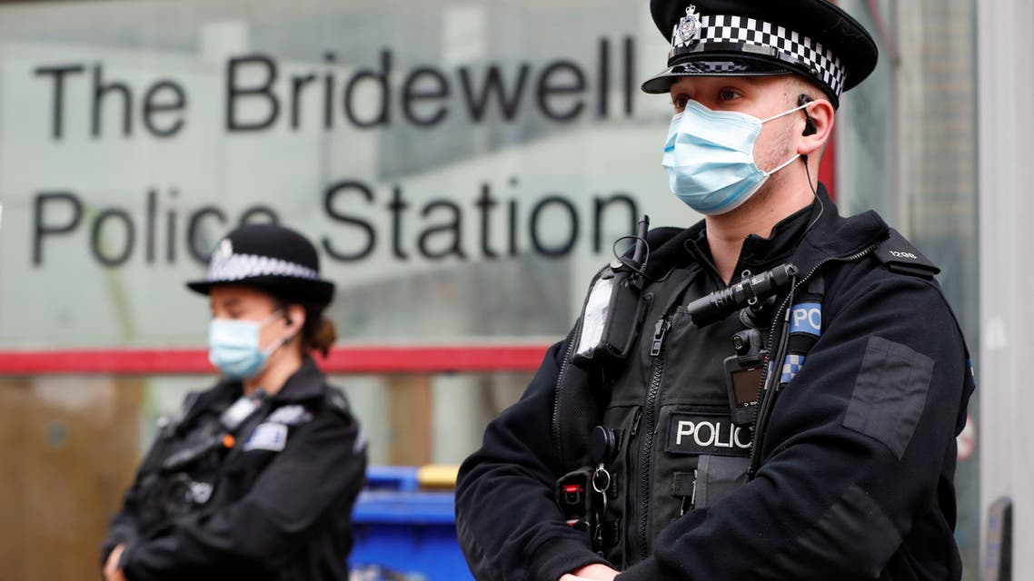 Police officers stand guard outside their station the morning after demonstrators clashed with police during a protest against a proposed new policing bill in Bristol, Britain, March 22, 2021. (Reuters)