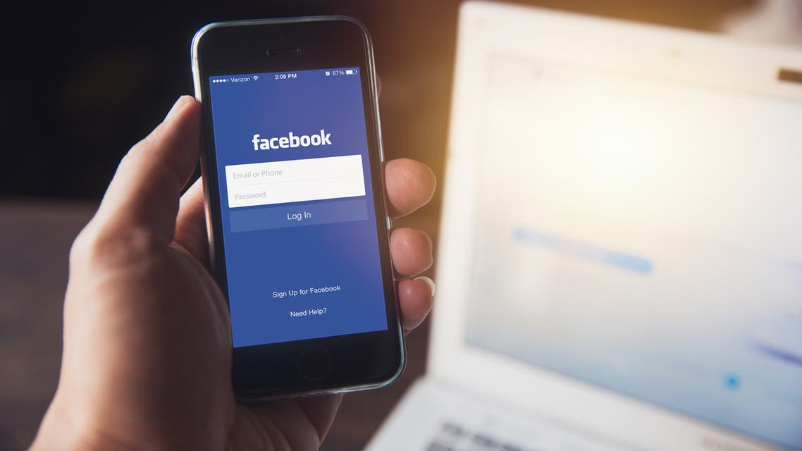 Facebook App on iPhone with computer laptop background closeup male hand hold social network on smart device concept. stock photo