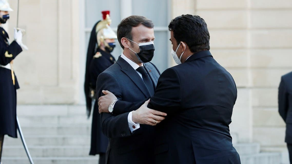 French President Emmanuel Macron meets Mohamed al-Menfi, Head of the Presidential Council of Libya for a meeting in Paris, March 23, 2021. (Reuters)