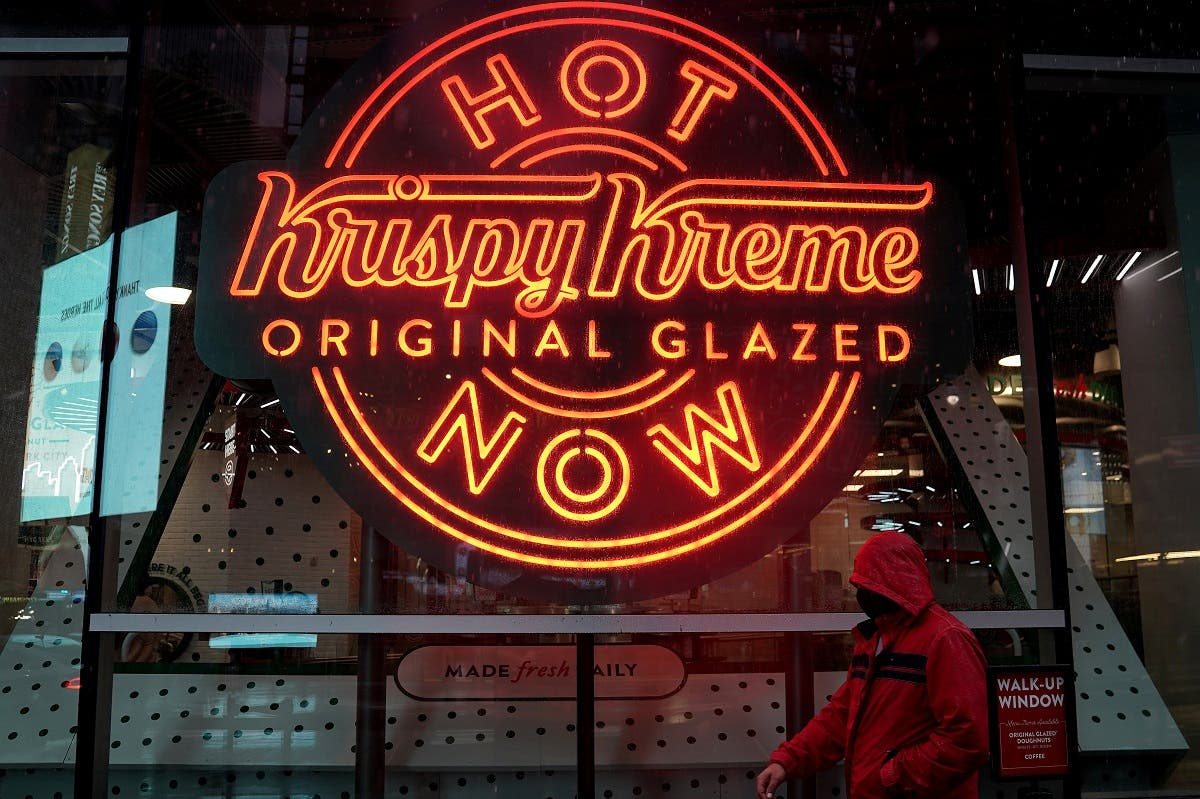"""A man walks past a Krispy Kreme """"Hot Now"""" neon sign in Times Square of New York City, Oct. 16, 2020. (Reuters)"""