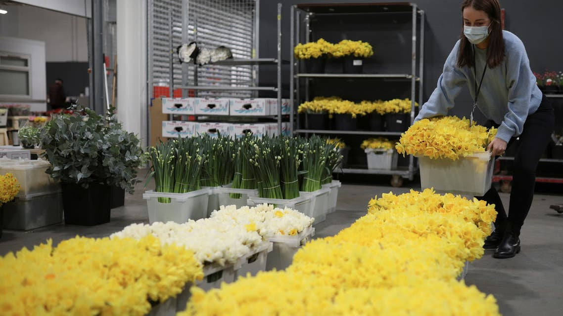Cassie Burt, marketing and communications manager of Covent Garden Market Authority, prepares flowers during the day of reflection to mark the anniversary of Britain's first coronavirus disease (COVID-19) lockdown, at the New Coven Garden Flower Market in London, Britain, March 23, 2021. (File photo: Reuters)