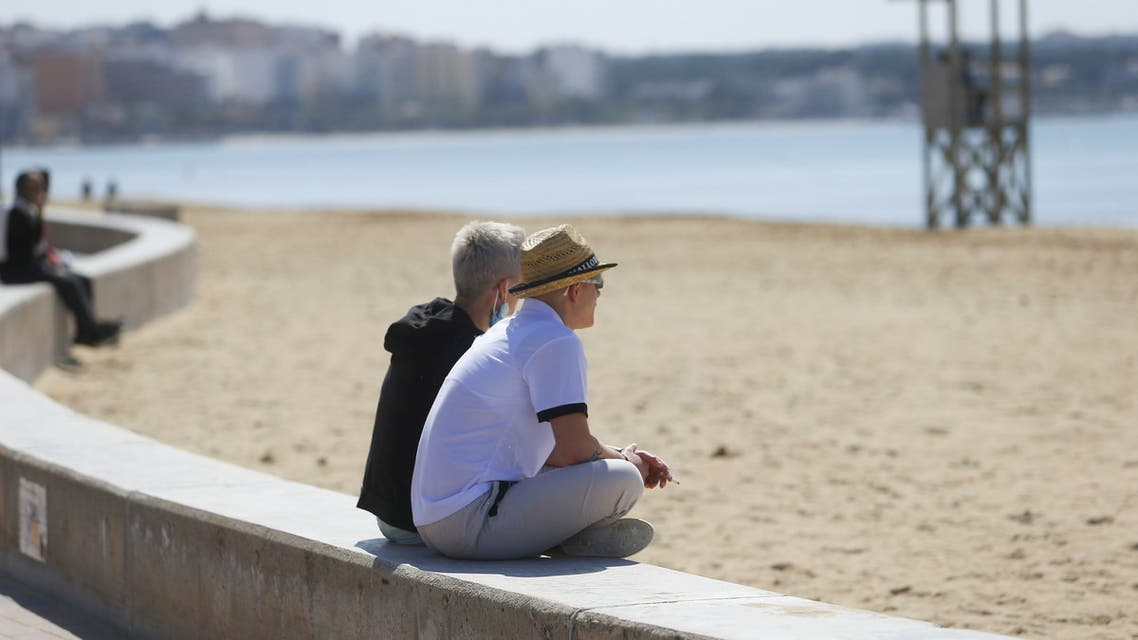 Tourists sit next to the sea in Playa de Palma beach in Palma de Mallorca following Berlin's lifted quarantine requirement for travelers returning from the Balearic Islands, amid the coronavirus disease (COVID-19) pandemic, Spain March 22, 2021. (File photo: Reuters)