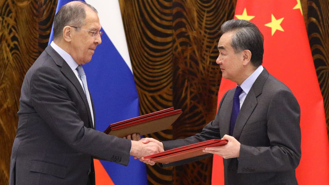 Russian Foreign Minister Sergei Lavrov and Chinese Foreign Minister Wang Yi exchange documents during a signing ceremony following their talks in Guilin on March 23, 2021. (AFP)