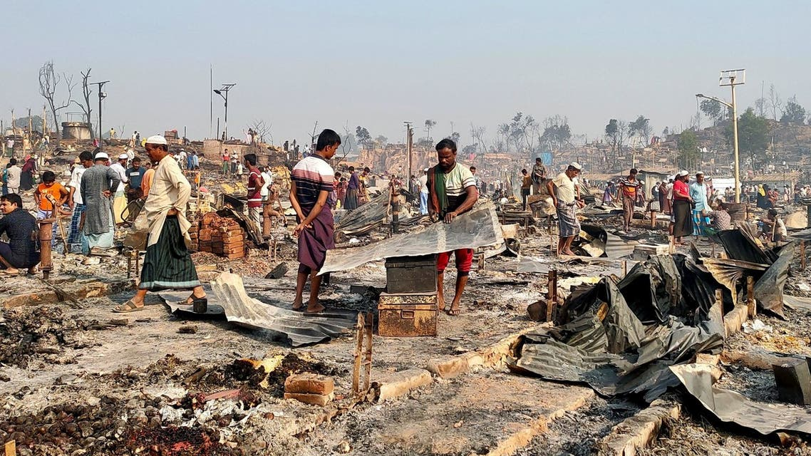 Rohingya refugees sift through rubble at the site where their shelter has been burned down following a fire that broke out at a Rohingya refugee camp in Cox's Bazar, Bangladesh, March 23, 2021. (Reuters)