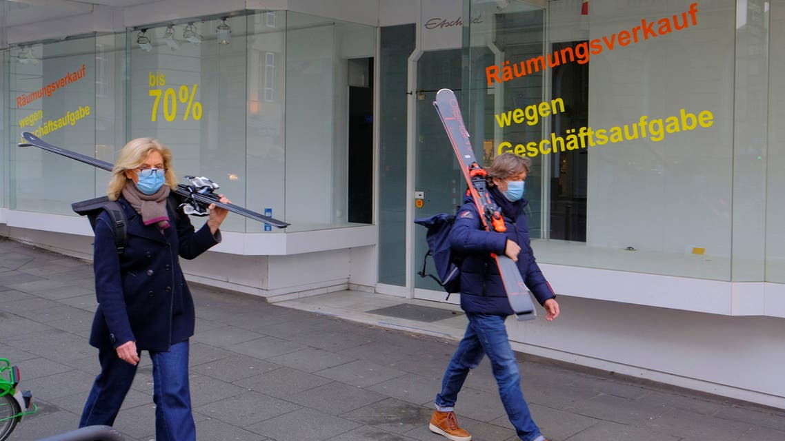 A couple walks past an abandoned store after buying new skis for the next season with a huge discount during winter sales, as the coronavirus disease (COVID-19) pandemic lockdown continues, in Bonn, Germany, March 16, 2021. (File photo: Reuters)