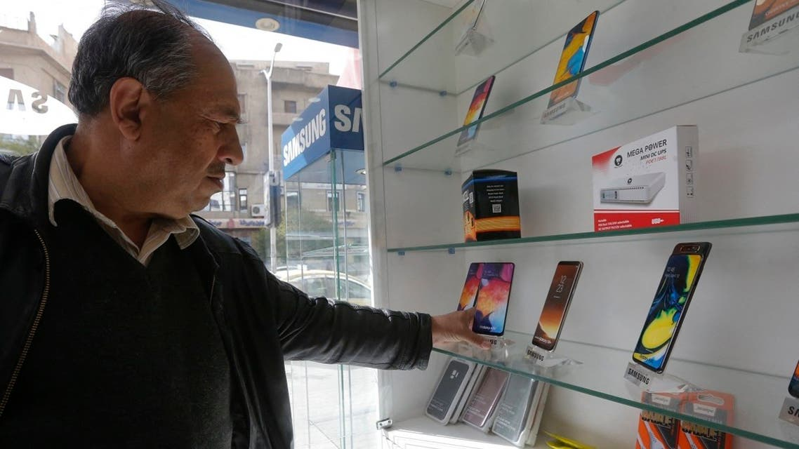 A man checks mobile phones displayed in a shop in the Syrian capital Damascus, on March 24, 2021. (Louai Beshara/AFP)