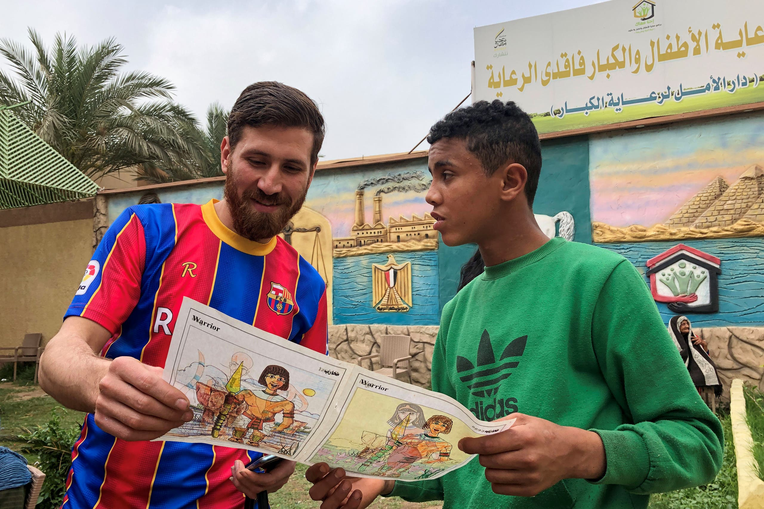 Islam Mohammed Ibrahim Battah, an Egyptian with a striking resemblance to BarcelonaÕs forward Lionel Messi, is seen with a youth in a club training facility, in the Nile Delta city of Zagazig, north of Cairo, Egypt March 23, 2021. (Reuters)