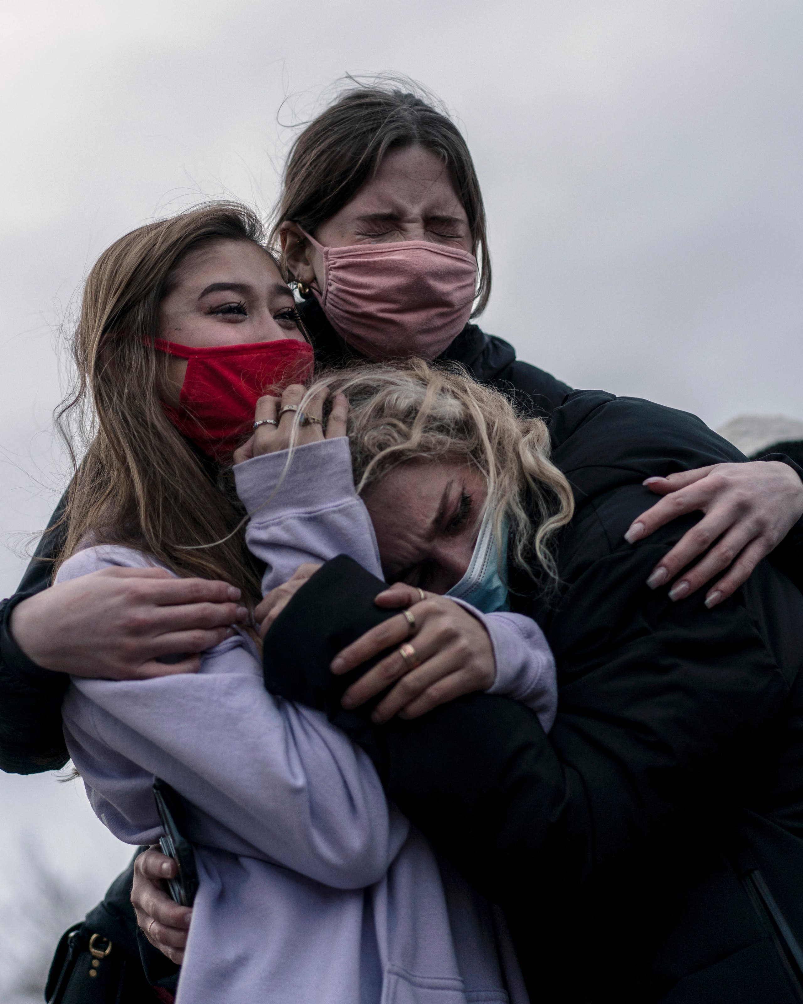 Mourners cry while looking at the scene of the crime the day after a gunman opened fired at a King Sooper's grocery store on March 22, 2021 in Boulder, Colorado. (File photo: AFP)