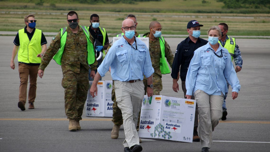 Australian officials carry boxes containing some 8,000 initial doses of the AstraZeneca vaccine following their arrival on board a Royal Australian Air Force plane at the Port Moresby international airport on March 23, 2021, as Papua New Guinea raced to quell a Covid-19 surge overwhelming its fragile health system. (File photo: AFP)
