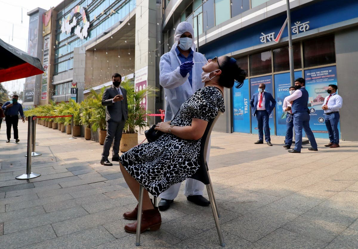 A healthcare worker collects a swab sample from a woman during a rapid antigen testing campaign for coronavirus, outside a shopping mall in Mumbai, India, on March 22, 2021. (Reuters)
