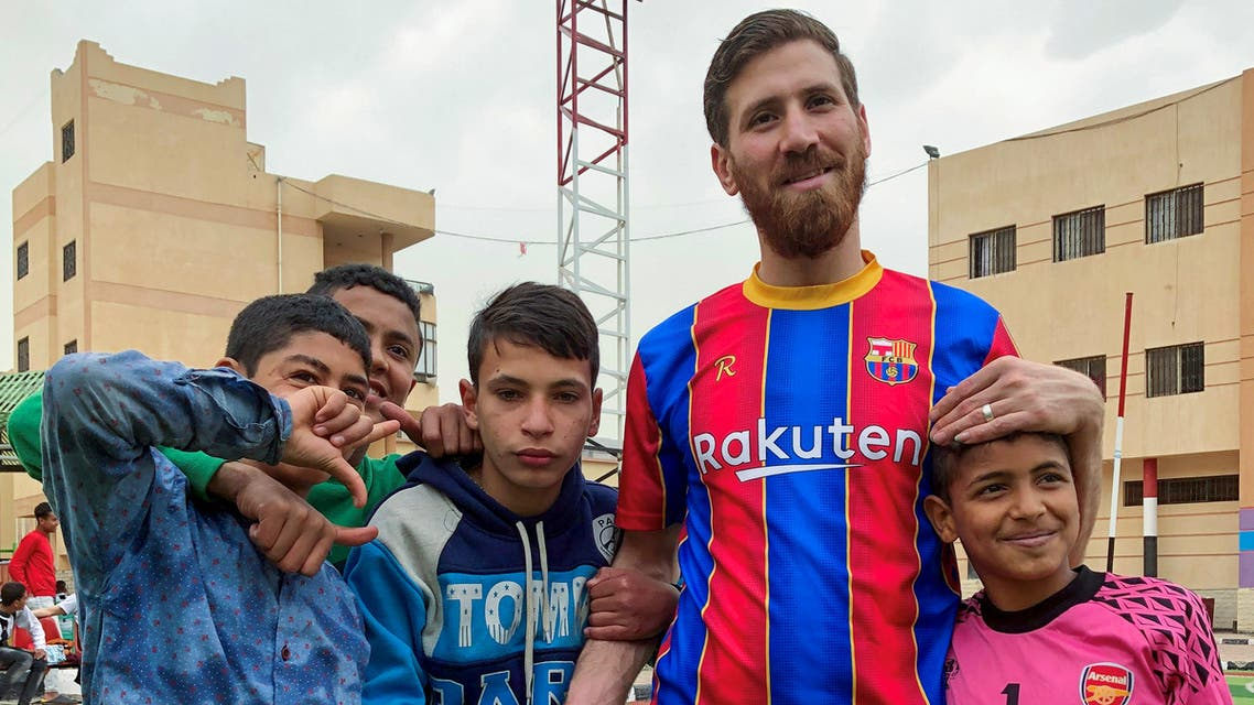 Islam Mohammed Ibrahim Battah, an Egyptian with a striking resemblance to Barcelona's forward Lionel Messi, poses for a photograph with boys, Cairo, March 23, 2021. (Reuters)