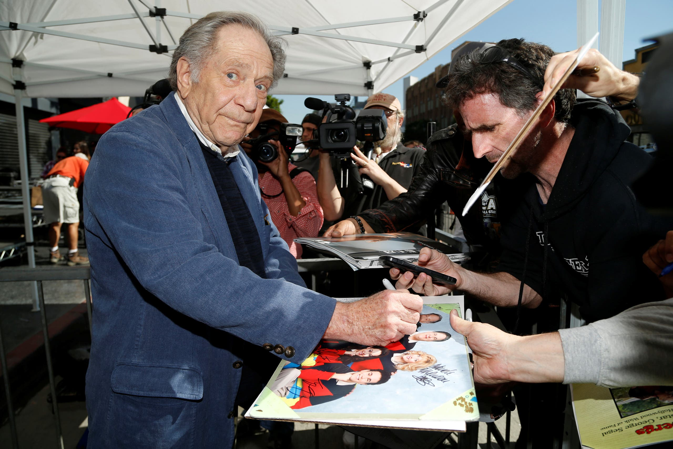 Actor George Segal signs autographs after unveiling his star on the Hollywood Walk of Fame in the Hollywood neighborhood of Los Angeles, California US, February 14, 2017. (Reuters)