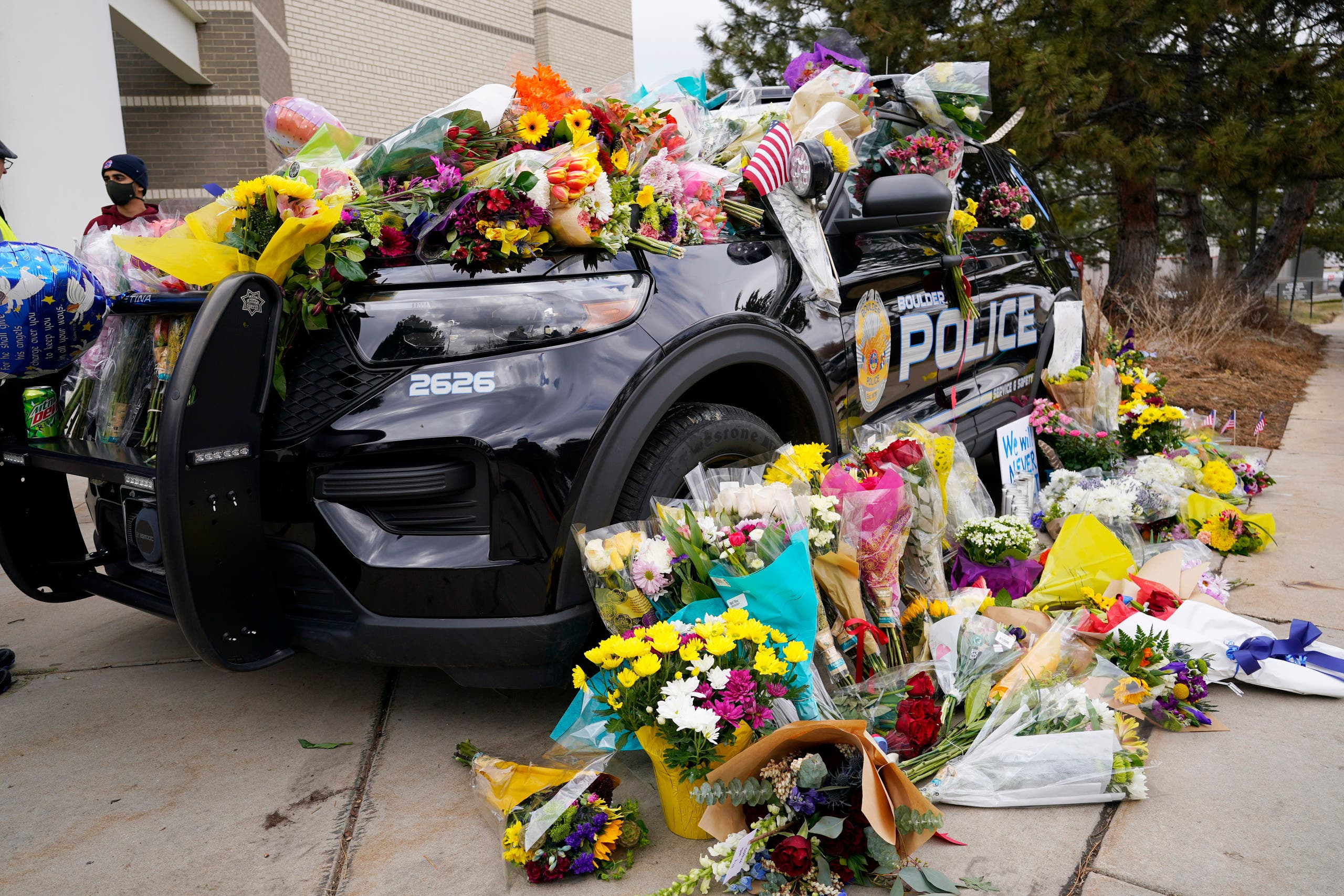 Police cruiser parked outside Boulder Police Department is covered with bouquets in tribute after an officer was one of the victims of a mass shooting at a King Soopers grocery store Tuesday, March 23, 2021, in Boulder, Colo. (File photo: AP)