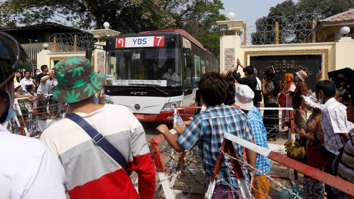 Onlookers watch as a bus ferrying coup detainees is driven out from Insein prison in Yangon on March 24, 2021, where they had been held for taking part in demonstrations against the military coup. (AFP)