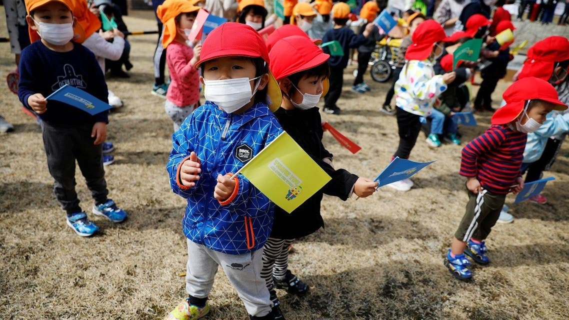 Children wearing face masks wait along the route of the Tokyo 2020 Olympic torch relay, amid the coronavirus disease (COVID-19) pandemic, on the first day of the relay in Naraha, Fukushima prefecture, Japan . (Reuters)