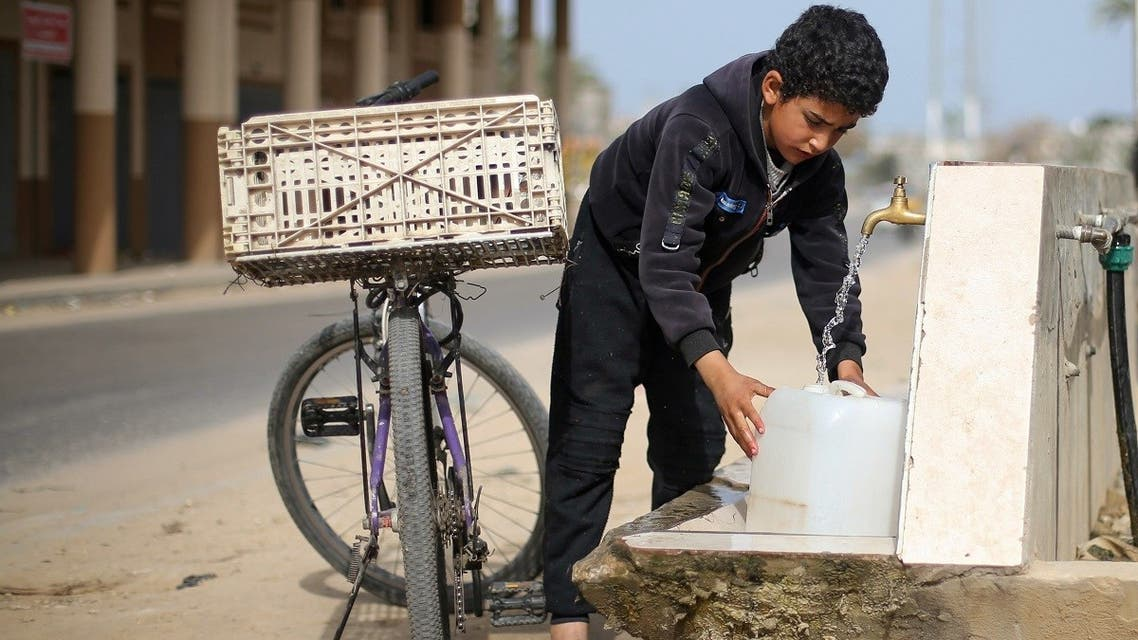 A Palestinian boy fills a container with water from a public tap On World Water Day, in the Gaza Strip March 22, 2021. (Reuters)